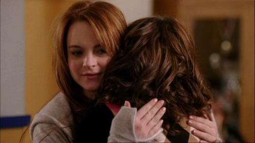In this picture from Mean Girls, Cady is hugging a girl who had been defending Regina George's backstabbing Cady, instead of helping her get closer to him. Usually, a hug is given for positive purposes, to symbolize good feelings. But it is clear that this hug is an act of façade because Cady's real face, which the other girl can't see, shows no sign of forgiveness.